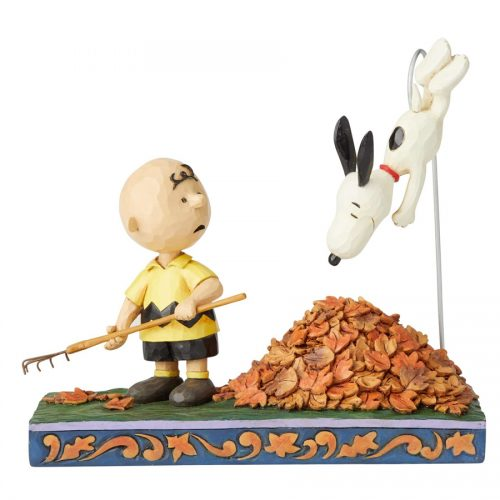 Charlie Brown raking leaves and Snoopy jumping in