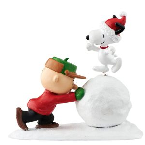 Charlie Brown pushing snowball with Snoopy on it