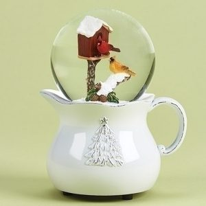 Small white pitcher with a snow globe on top and a birdhouse with cardinals inside